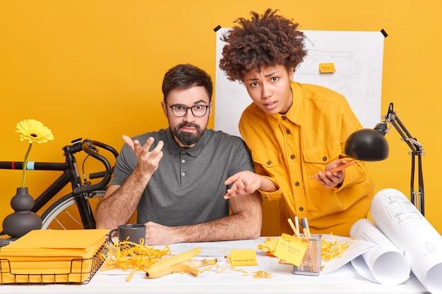 Verbaasde interraciale vrouw en man kijken verbaasd terwijl ze op kantoor werken, tekenen schets van toekomstige bouwconstructie, kijken verontwaardigd poseren op desktop geconcentreerd op werk