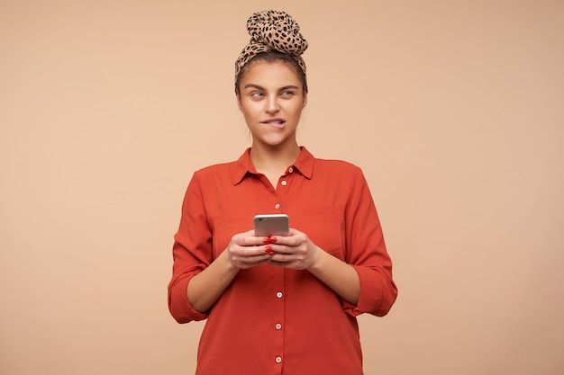 Verbaasde jonge aantrekkelijke bruinharige dame met mobiele telefoon in haar handen, ogen dichtknijpen en peinzend onderlip bijten terwijl ze poseren over beige muur