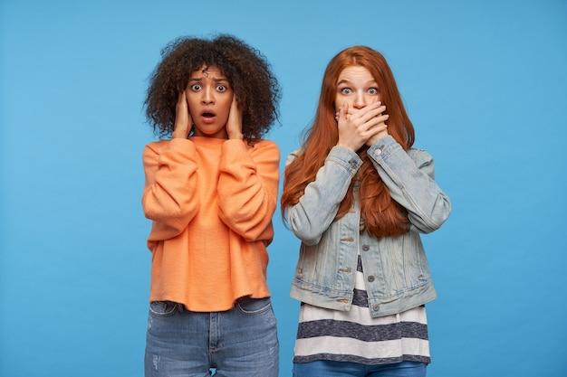 Verbaasde jonge aantrekkelijke vrouwen die hun oren en mond bedekken met opgeheven handpalmen en verrast ogen rondkijken terwijl ze kijken, geïsoleerd over blauwe muur