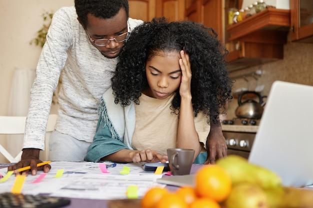Verbaasde jonge afrikaanse vrouw met hoofdpijn tijdens het berekenen van het gezinsbudget aan de keukentafel