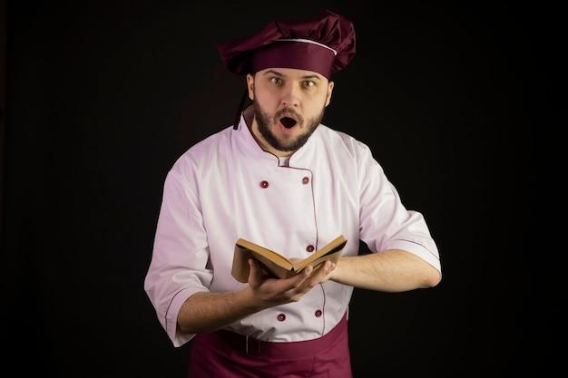 Verbaasde jonge, bebaarde chef-kok in uniform houdt een boek met vintage oude recepten open