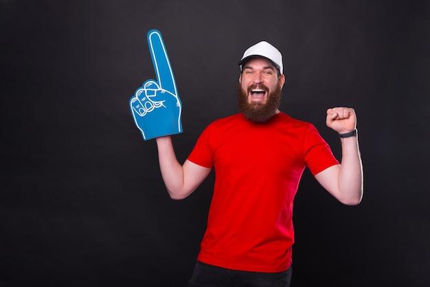 Verbaasde jonge bebaarde man in rood t-shirt vieren en wijzen met ventilator schuim handschoen