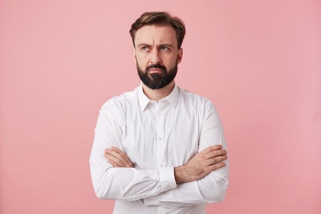 Verbaasde jonge bebaarde man met kort bruin haar die zijn handen op zijn borst vouwt, terwijl hij bedachtzaam opzij kijkt en wenkbrauw optrekt, staande over een roze muur in een wit overhemd