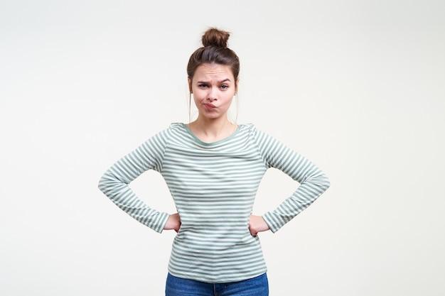 Verbaasde jonge blauwogige mooie bruinharige dame die haar mond verdraait terwijl ze naar voren kijkt en de handen op haar middel vasthoudt terwijl ze poseert over een witte muur