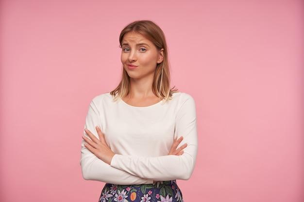 Verbaasde jonge blonde vrouw met casual kapsel handen op de borst vouwen en met twijfelende gezicht naar camera kijken, gekleed in witte blouse en gebloemde rok terwijl staande op roze achtergrond