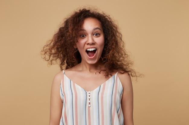 Verbaasde jonge bruinharige krullende vrouw kijkt opgewonden met wijd open mond, geïsoleerd op beige in gestreepte zomertop