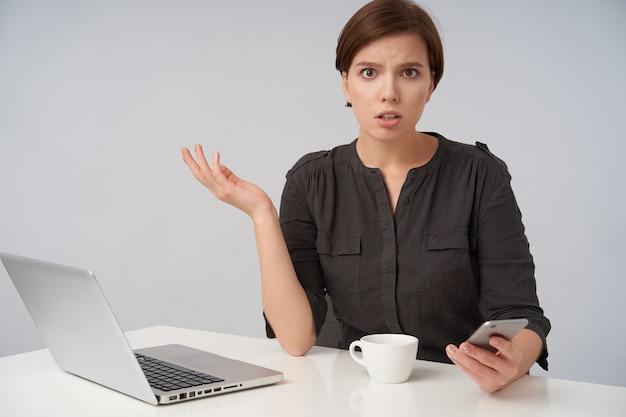 Verbaasde jonge bruinharige mooie vrouw met natuurlijke make-up verward haar handpalm verhogen terwijl ze verward kijkt, zittend op wit met smartphone en laptop