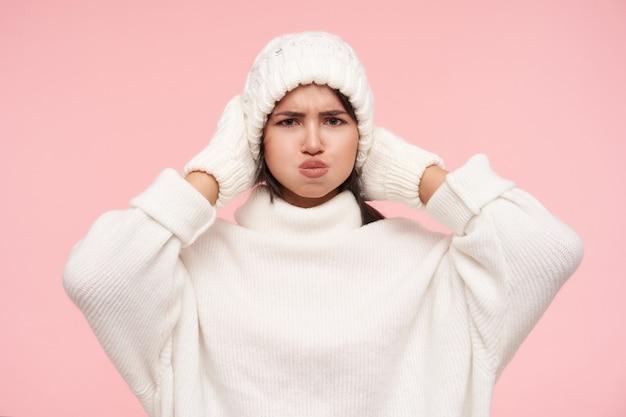 Verbaasde jonge bruinharige vrouw in witte rolkraag, handschoenen en hoed fronst haar wenkbrauwen terwijl ze gezichten trekt en wangen opblaast, geïsoleerd over roze muur