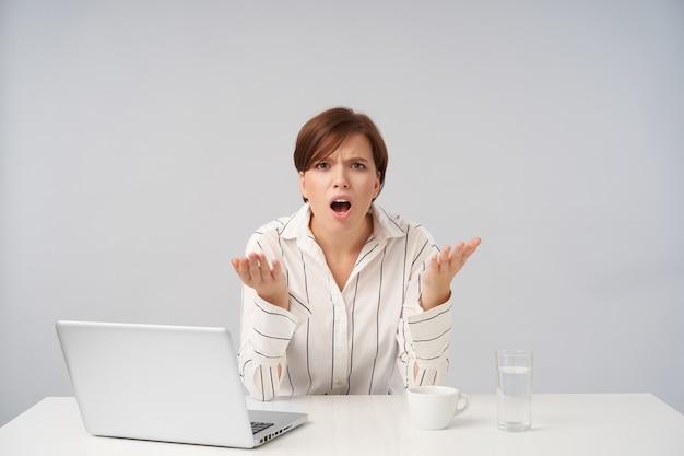 Verbaasde jonge bruinharige vrouw met kort trendy kapsel opgewonden handen opheffen terwijl ze haar wenkbrauwen fronst met geopende mond, zittend op wit