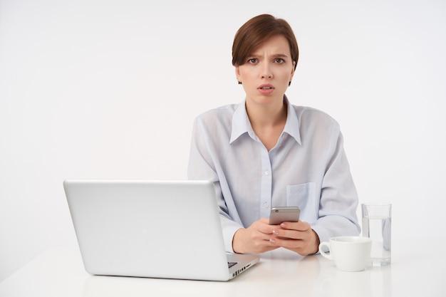 Verbaasde jonge bruinogige brunette vrouw met casual kapsel haar wenkbrauwen fronsen en droevig kijken, mobiele telefoon vasthouden terwijl zittend op wit
