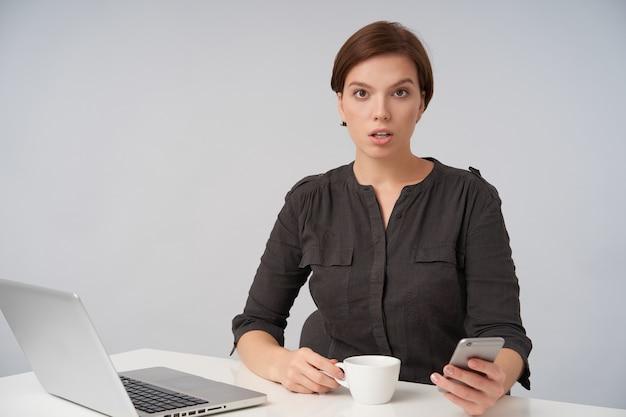 Verbaasde jonge bruinogige kortharige brunette vrouw die verwarrend wenkbrauw opheft, mobiele telefoon in haar hand houdt terwijl ze poseren op wit