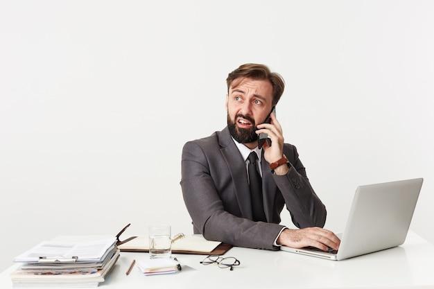 Verbaasde jonge brunette man met baard opzij kijken met verward gezicht en zijn voorhoofd rimpelen, bellen met smartphone zittend aan tafel met handen op toetsenbord van zijn laptop