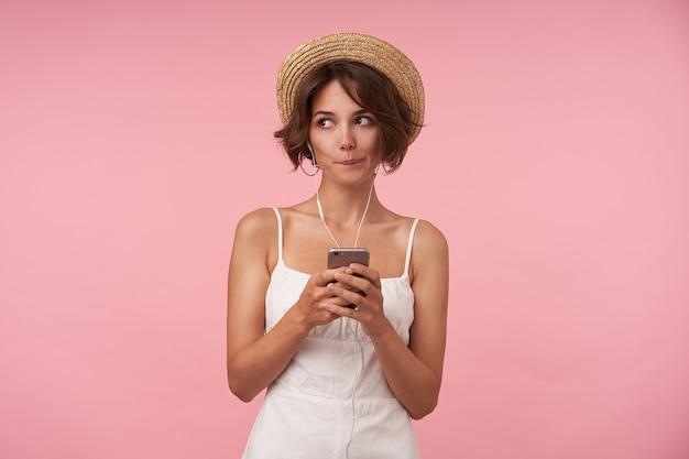 Verbaasde jonge brunette vrouw met kort kapsel opzij kijken en onderlip bijten terwijl mobiele telefoon in opgeheven handen, witte zomerjurk en strooien hoed dragen