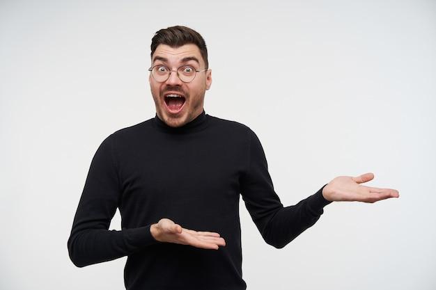 Verbaasde jonge donkerharige bebaarde man die zijn handpalmen omhoog houdt terwijl hij opgewonden kijkt met grote ogen en open mond, geïsoleerd op wit