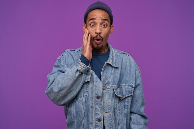 Verbaasde jonge donkerhuidige, bebaarde brunette man die zijn ogen rondt terwijl hij verbaasd kijkt, hand op zijn wang houdt terwijl hij poseert voor de paarse muur