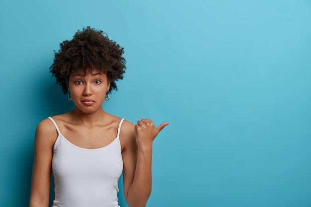 Verbaasde jonge etnische vrouw wijst duim op kopie ruimte, gekleed in casual vest, aarzelt over productprijs, ziet iets vreemds, poses