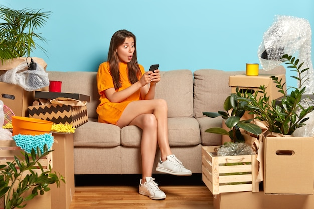 Verbaasde jonge kaukasische huiseigenaar verhuist naar nieuw appartement, verandert van huis, staart naar smartphone, maakt plannen voor huisverbetering, zit op een comfortabele bank, gekleed in een oranje t-shirt, witte sneakers
