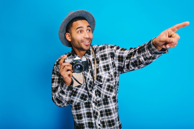 Verbaasde jonge knappe man met plezier met camera. reizen, genieten van vakantie, toerisme, kaart, opgewekte stemming, geluk, ware emoties, positiviteit, jorney.