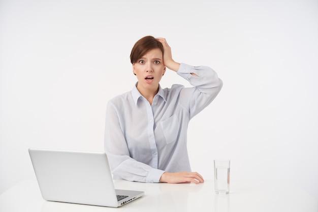 Verbaasde jonge kortharige brunette dame houdt de handpalm op haar hoofd en kijkt verward, gekleed in formele kleding terwijl ze op wit zit
