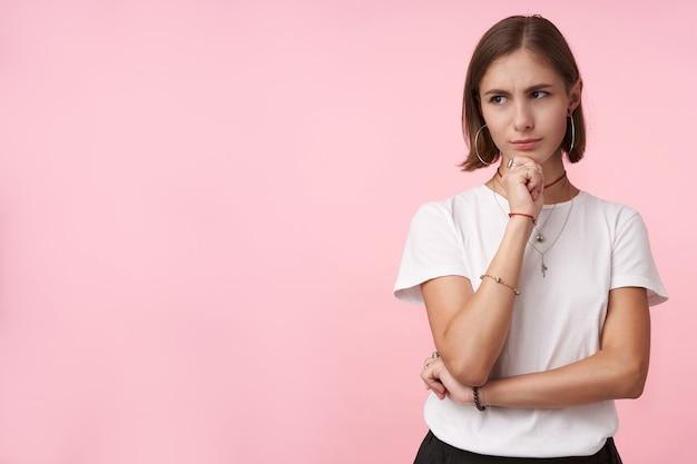 Verbaasde jonge kortharige brunette vrouw met natuurlijke make-up die haar kin met opgeheven handen vasthoudt terwijl ze bedachtzaam opzij kijkt, staande over roze muur