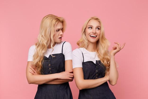 Verbaasde jonge langharige blonde vrouw die de handen op haar borst kruist terwijl ze verward naar haar withoofdige vrolijke zus kijkt, die over roze achtergrond staat