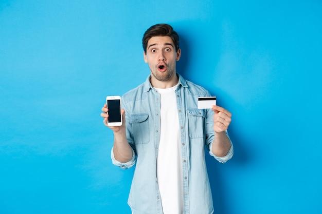 Verbaasde jonge man die het scherm van de mobiele telefoon en creditcard toont, online winkelt, staande tegen een blauwe achtergrond