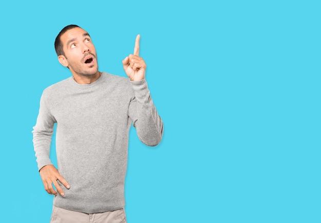 Verbaasde jonge man die met zijn vinger omhoog wijst