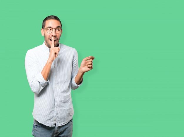 Verbaasde jonge man die om stilte vraagt gebaren met zijn vinger