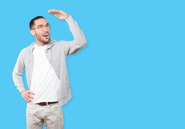Verbaasde jonge man met een gebaar van wegkijken