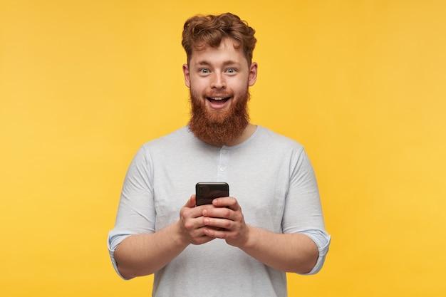 Verbaasde jonge man met een grote rode baard met een geschokte gezichtsuitdrukking, houdt zijn telefoon vast