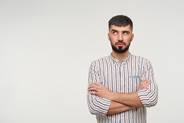 Verbaasde jonge mooie brunette bebaarde man die zijn wenkbrauw opheft terwijl hij peinzend naar boven kijkt en de handen op zijn borst vouwt, geïsoleerd over witte muur