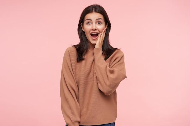Verbaasde jonge mooie brunette vrouw met casual kapsel houdt haar mond wijd open terwijl ze verdwaasd naar voren kijkt, hand opsteken naar haar gezicht terwijl ze poseren over roze muur