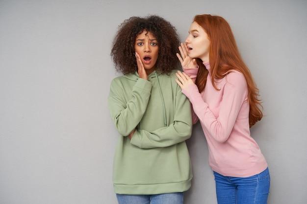 Verbaasde jonge mooie donkerhuidige brunette gekrulde vrouw kijkt opgewonden en houdt opgeheven handpalm op haar wang terwijl ze luistert naar schokkend nieuws van haar vriend