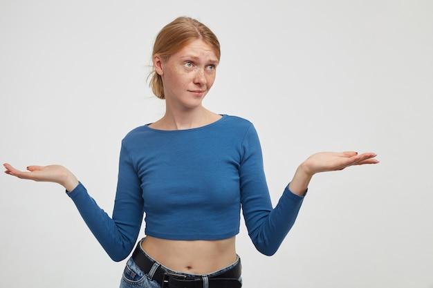 Verbaasde jonge mooie roodharige dame gekleed in vrijetijdskleding poseren op witte achtergrond, perplex handpalmen verhogen en grimassen haar gezicht met gevouwen lippen
