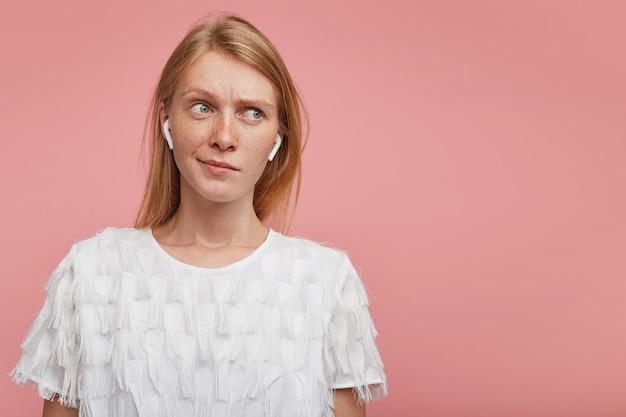 Verbaasde jonge mooie roodharige dame met casual kapsel fronst haar wenkbrauwen terwijl ze verward opzij kijkt, koptelefoon op terwijl ze over roze achtergrond staat