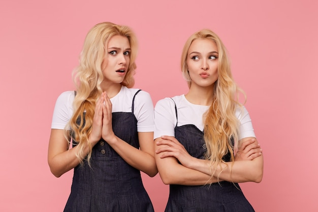 Verbaasde jonge mooie vrouw met bruine ogen en golvend haar die de handen omhoog houdt terwijl ze verward naar de camera kijkt, staande over de roze achtergrond met haar mooie blonde, ontevreden zus