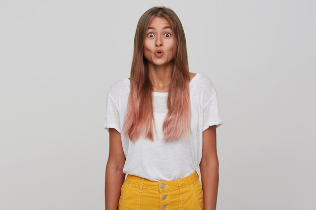 Verbaasde jonge mooie vrouw met lichtbruin lang haar dat haar lippen vouwt terwijl ze verrast kijkt, vrijetijdskleding draagt terwijl ze zich voordeed over een witte muur