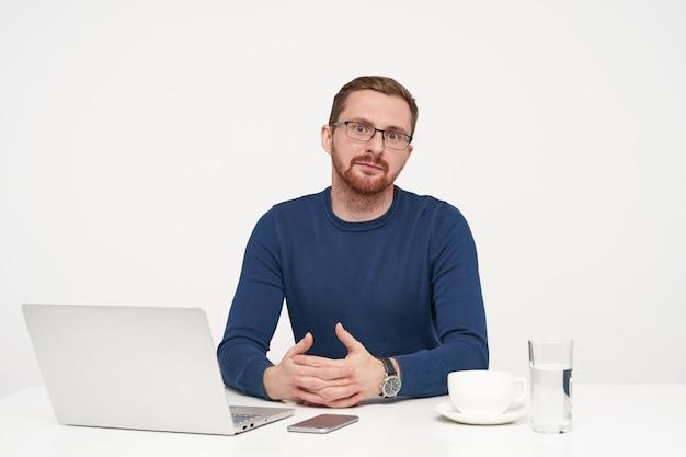 Verbaasde jonge ongeschoren blonde man gekleed in blauwe trui verrast camera kijken en houdt zijn handen op tafelblad, zittend op witte achtergrond