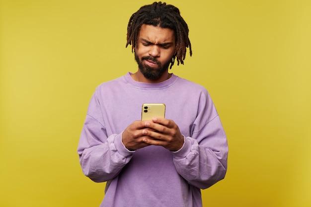 Verbaasde jonge vrij donkere bebaarde man met een baard fronst zijn gezicht terwijl hij verward kijkt op het scherm van zijn mobiele telefoon, geïsoleerd op gele achtergrond