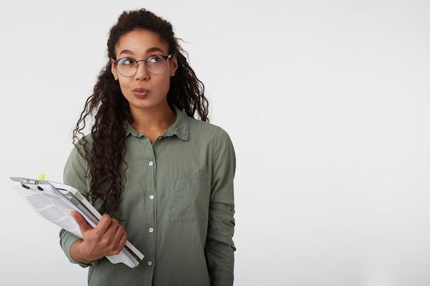 Verbaasde jonge vrij donkere gekrulde vrouw met casual kapsel die haar lippen prikt terwijl ze peinzend naar boven kijkt en schoolboeken in opgeheven hand houdt, geïsoleerd op wit