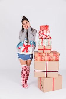 Verbaasde jonge vrouw dichtbij hoop van cadeaus