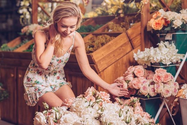 Verbaasde jonge vrouw die mooie rozen in de bloemistwinkel bekijkt