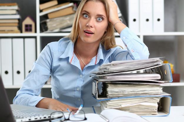 Verbaasde jonge vrouw die veel werk in bureau heeft