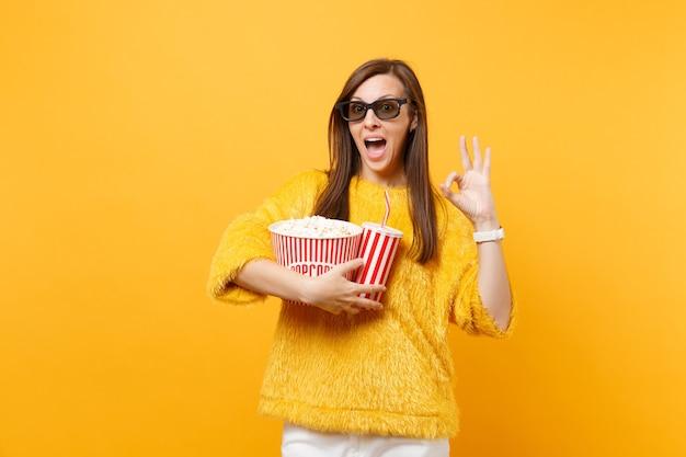 Verbaasde jonge vrouw in 3d imax-bril kijken naar filmfilm, met emmer popcorn, kopje cola of frisdrank, met ok-teken geïsoleerd op gele achtergrond. mensen oprechte emoties in de bioscoop, levensstijl.