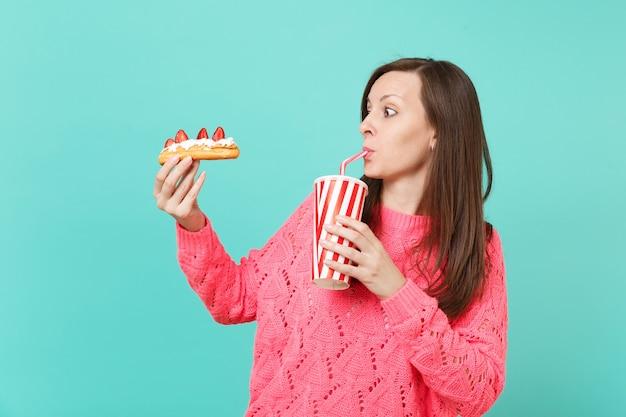Verbaasde jonge vrouw in gebreide roze trui op zoek op eclair cake en cola of frisdrank drinken uit plastic beker geïsoleerd op blauwe achtergrond, studio portret. mensen levensstijl concept. bespotten kopie ruimte.