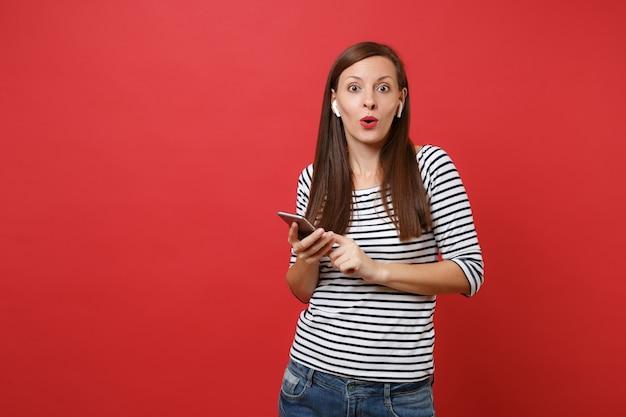 Verbaasde jonge vrouw in gestreepte kleding met draadloze koptelefoon met mobiele telefoon, luisteren naar muziek geïsoleerd op heldere rode achtergrond. mensen oprechte emoties, lifestyle concept. bespotten kopie ruimte.
