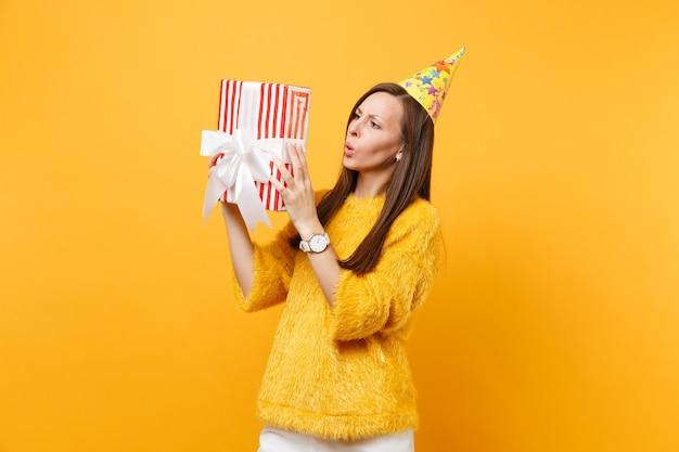 Verbaasde jonge vrouw in verjaardagsfeestje hoed probeert te raden wat er in de rode doos met cadeau aanwezig is vieren en genieten van vakantie geïsoleerd op felgele achtergrond. mensen oprechte emoties, levensstijl.