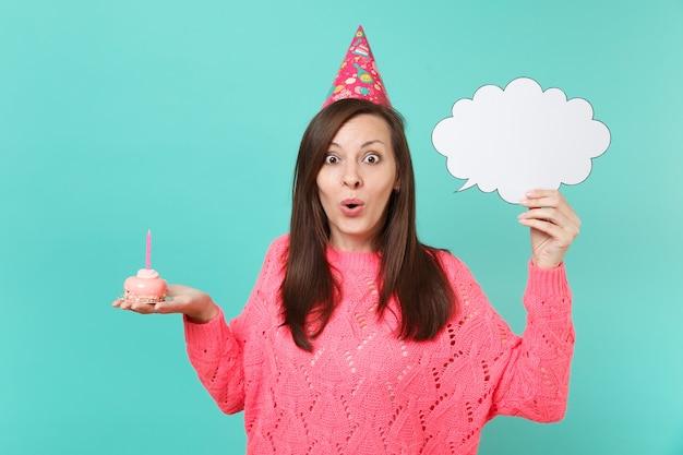 Verbaasde jonge vrouw in verjaardagshoed in hand taart met kaars, lege blanco say cloud tekstballon voor promotionele inhoud geïsoleerd op blauwe achtergrond. mensen levensstijl concept. bespotten kopie ruimte.