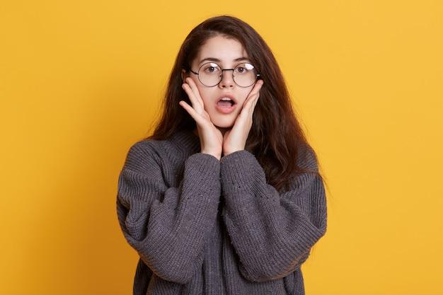Verbaasde jonge vrouw kleedt zwarte trui en bril