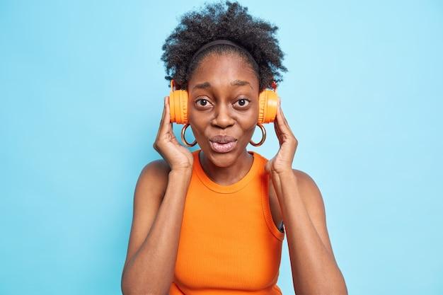 Verbaasde jonge vrouw met donkere huid houdt stereokoptelefoon vast